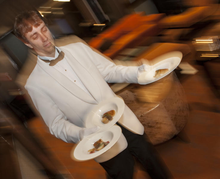 Evan Boyle serves the first course during a re-creation of the final first class dinner served on the RMS Titanic, Saturday, April 14, 2012, in Houston. The Titanic sank in the North Atlantic Ocean April 15, 1912 after colliding with an iceberg during her maiden voyage from Southampton, England to New York. (AP Photo/Dave Einsel)