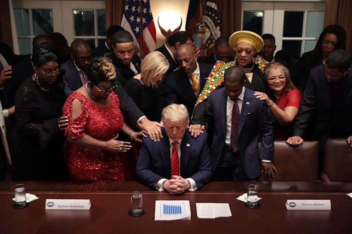 African American supporters lay their hands on President Donald Trump as they pray for him after a meeting in the Cabinet Room at the White House February 27, 2020. (Chip Somodevilla/Getty Images)