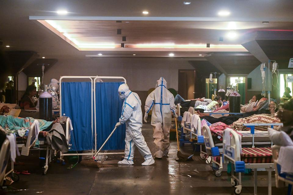 TOPSHOT - A health worker wearing a personal protective equipment (PPE) suit cleans the floor inside a banquet hall temporarily converted into a Covid-19 coronavirus ward in New Delhi on May 1, 2021. (Photo by Prakash SINGH / AFP) (Photo by PRAKASH SINGH/AFP via Getty Images)