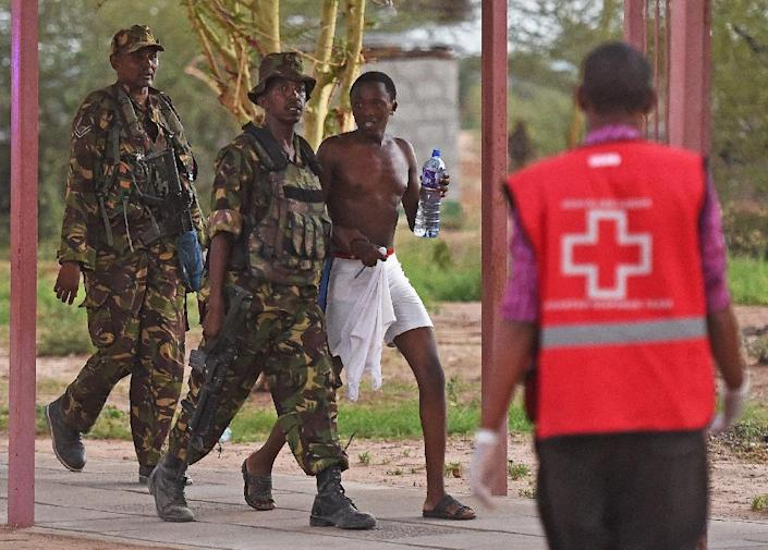 A male student hostage is escorted out of Garissa University after Kenya Defence Forces ended a siege by gunmen on April 2, 2015 (AFP Photo/Carl de Souza)
