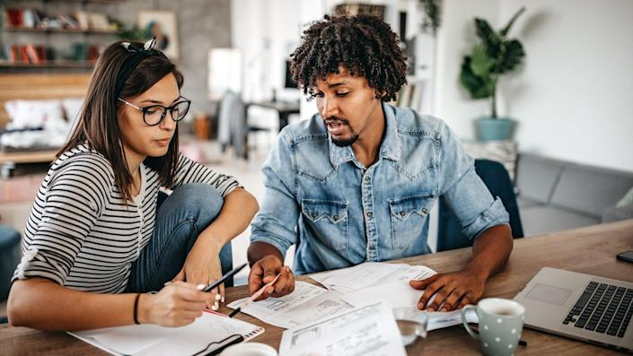 Modern married multi-ethnic young couple calculating financial bills at home.
