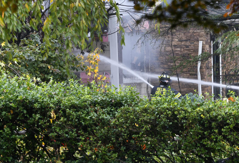 Woodbridge firefighters work to extinguish the scene of a plane crash at a home Tuesday, Oct. 29, 2019, in Woodbridge,N.J. Authorities say a pilot is unaccounted for after the small plane he was flying crashed into a house in New Jersey and exploded. (AP Photo/Noah K. Murray)