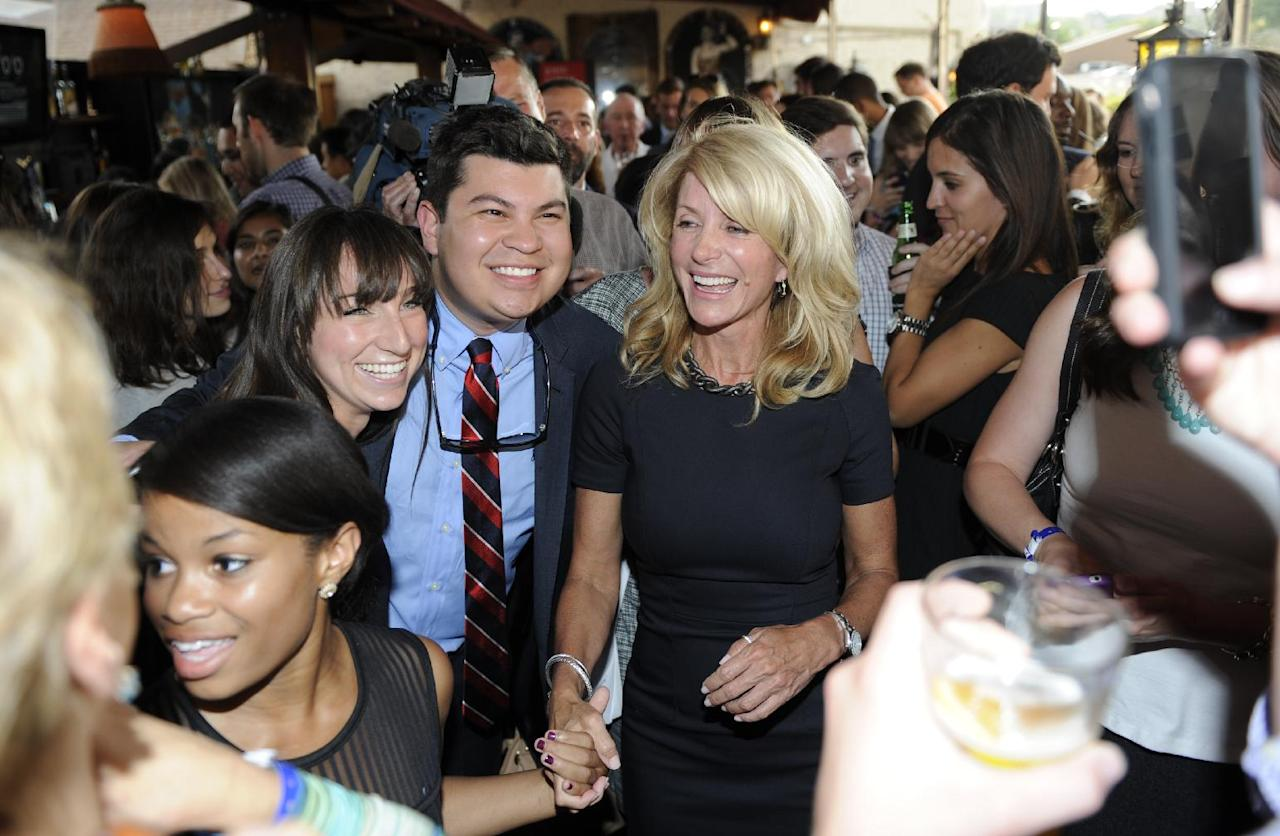 File - In this July 25, 2013 file photo, Texas State Senator Wendy Davis, right, meets and poses for pictures with attendees at a fundraiser, in Washington. Davis' compelling personal story of rising from a trailer park to Harvard Law has reeled in donors. She now has financial backers in every U.S. state. (AP Photo/Nick Wass, File)