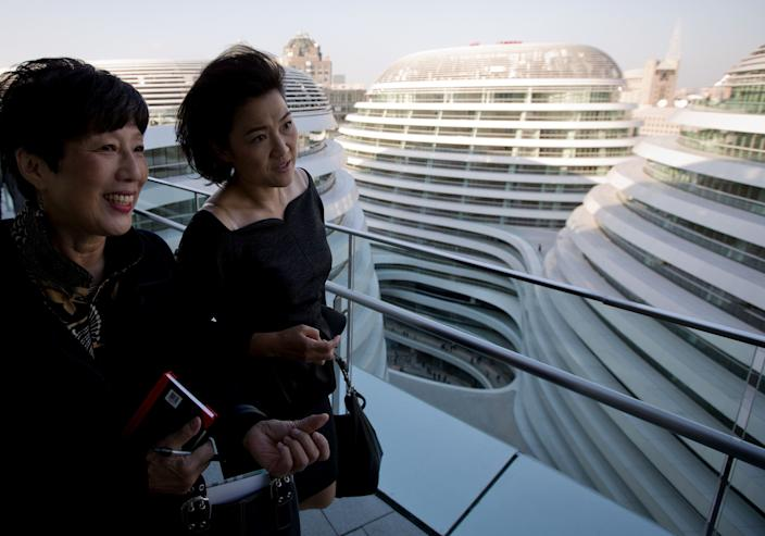 Soho China CEO Zhang Xin, second from left, walks with a guest as they tour the newly opened Galaxy Soho building in Beijing Saturday, Oct. 27, 2012. (AP Photo/Andy Wong)