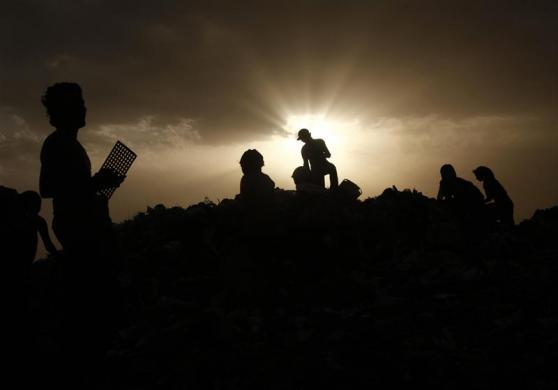 Ragpickers collect recyclables as they are silhouetted against the setting sun at a dump yard on World Environment Day in New Delhi June 5, 2012.