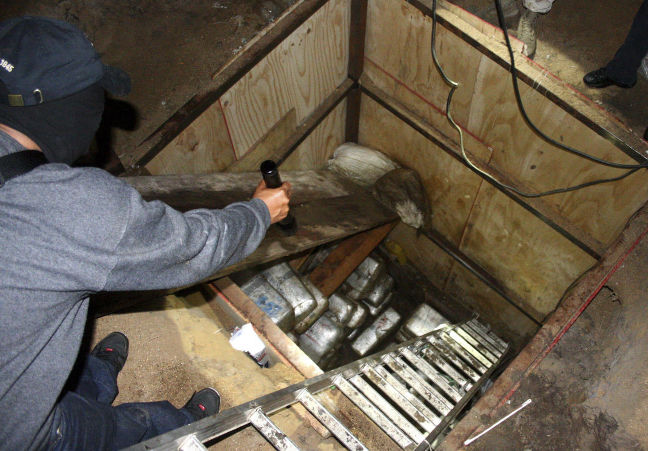A Mexican soldier flashes his torchlight inside a tunnel in Tijuana November 3, 2010. U.S. border police have found a sophisticated drug smugglers' tunnel the length of six football fields linking Southern California with Mexico and arrested two people, authorities said on Wednesday. Agents recovered more than 25 tonnes of marijuana in seizures related to the investigation in both California and Mexico and arrested a U.S. citizen and his Mexican wife. Picture taken November 3, 2010.  REUTERS/Jorge Duenes (MEXICO - Tags: POLITICS CRIME LAW SOCIETY)
