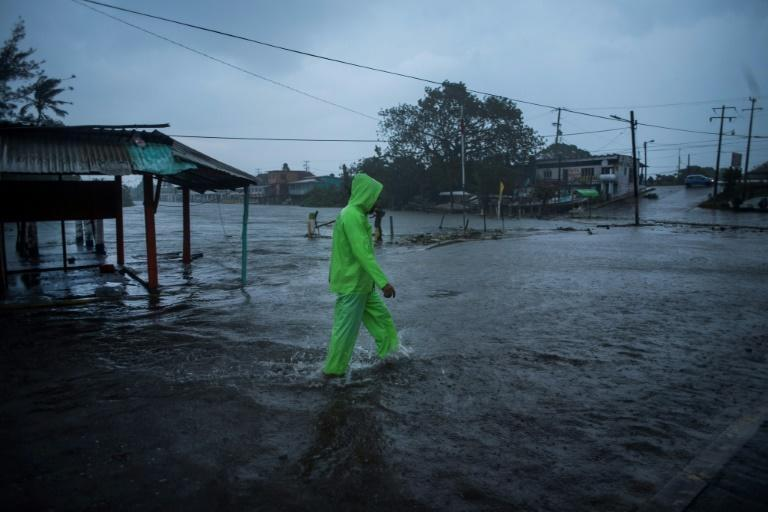 A man walks in a flooded street due to heavy rains caused by Hurricane Grace in Tecolutla in eastern Mexico