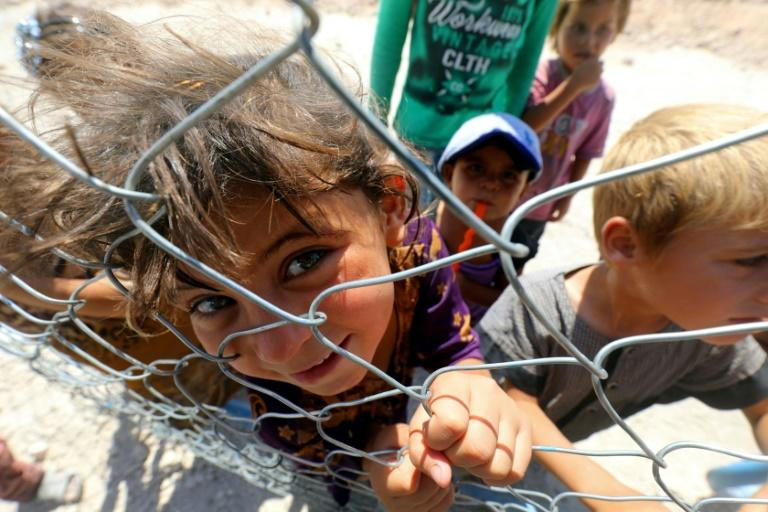 Displaced children from the Islamic State group's Syrian stronghold of Raqa pose for a photo behind a fence at a camp in Ain Issa on August 22, 2017