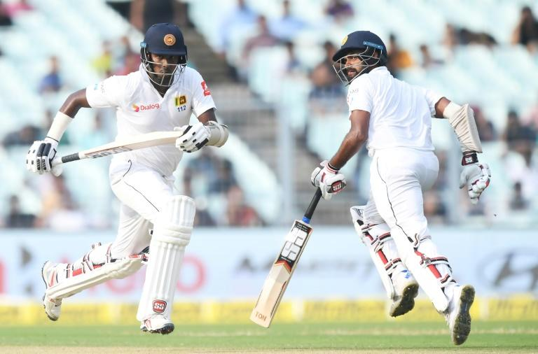 Sri Lanka's Angelo Mathews (L) and Lahiru Thirimanne run between the wickets during the third day of the first Test between India and Sri Lanka at the Eden Gardens cricket stadium in Kolkata