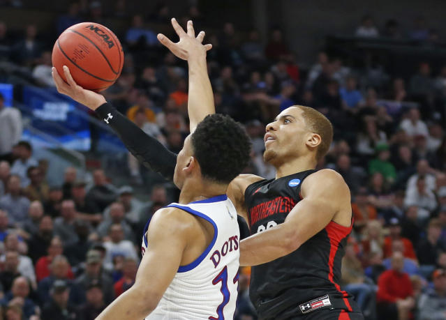 Northeastern guard Donnell Gresham Jr., right, lays up the ball as Kansas guard Devon Dotson (11) defends in the first half during a first round men's college basketball game in the NCAA Tournament, Thursday, March 21, 2019, in Salt Lake City. (AP Photo/Rick Bowmer)