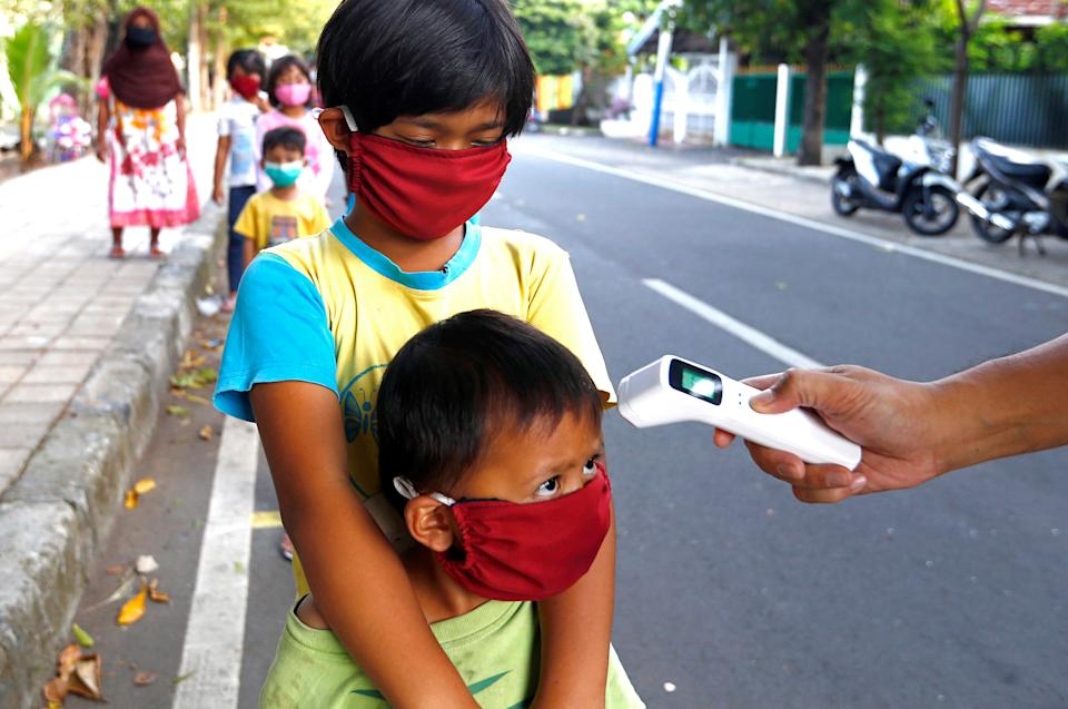 Children wearing a protective face mask are checked with thermal scanner before getting free food amid the coronavirus disease (COVID-19) outbreak in Jakarta, Indonesia, May 14, 2020.