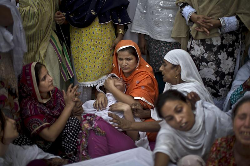 A Pakistani woman, center, comforts another as they mourn over the coffins of their relatives, who were killed in a suicide attack on a church, in Peshawar, Pakistan, Sunday, Sept. 22, 2013. A suicide bomb attack on a historic church in northwestern Pakistan killed scores of people Sunday, officials said, in one of the worst assaults on the country's Christian minority in years. (AP Photo/Muhammed Muheisen)
