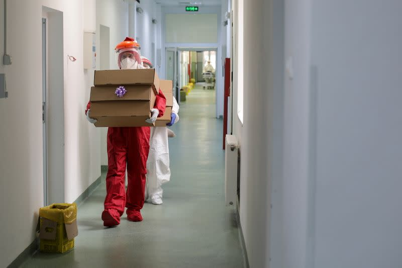Ionut Ivan, a 40-year-old nurse, dressed in red Personal Protective Equipment (PPE) carries boxes with sweets and fruits for patients, in Bucharest