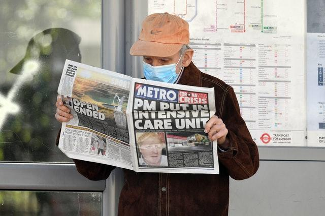 A man wearing a facemask at a bus stop reading a newspaper outside St Thomas' Hospital in Central London where Prime Minister Boris Johnson was in intensive care