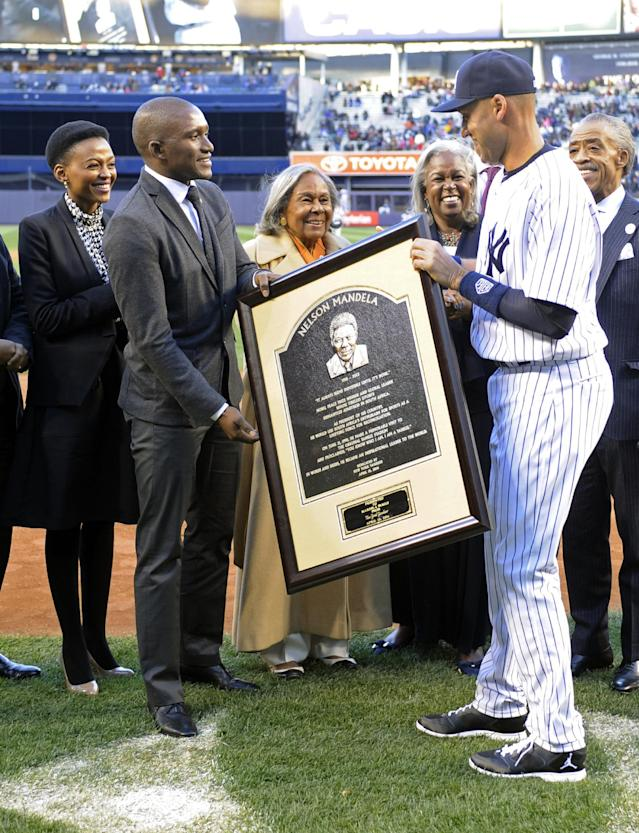 New York Yankees' Derek Jeter, right, presents a photo of a Nelson Madela plaque to, from left, Lindo Mandela, Zondwa Mandela, Rachel Robinson and Sharon Robinson before Game 2 of an interleague baseball doubleheader against the Chicago Cubs, Wednesday, April 16, 2014, at Yankee Stadium in New York. Lindo is the wife of Zondwa, Zondwa is the grandson of Nelson, Rachel is the widow of baseball great Jackie Robinson and Sharon is the daughter of Rachel and Jackie. (AP Photo/Bill Kostroun)