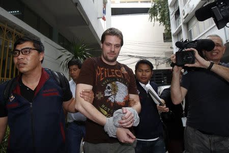 Hans Fredrik Lennart Neij (C), a co-founder of the Swedish file-sharing website, The Pirate Bay, is escorted by Thai police officers as he arrives at the Immigration Detention Center in Bangkok November 5, 2014. REUTERS/Chaiwat Subprasom