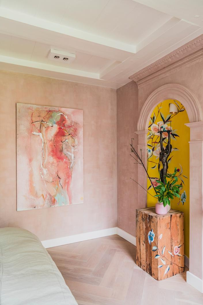 "<div class=""caption""> In the bedroom, a statue titled <em>La Trapeziste</em> by Dutch-French-Italian sculptor Dahné du Barry is displayed in a niche that is painted yellow to match a pillow by <a href=""https://www.jimthompson.com/decor/living-room/cushions.html"" rel=""nofollow noopener"" target=""_blank"" data-ylk=""slk:Jim Thompson"" class=""link rapid-noclick-resp"">Jim Thompson</a> on the bed. </div>"