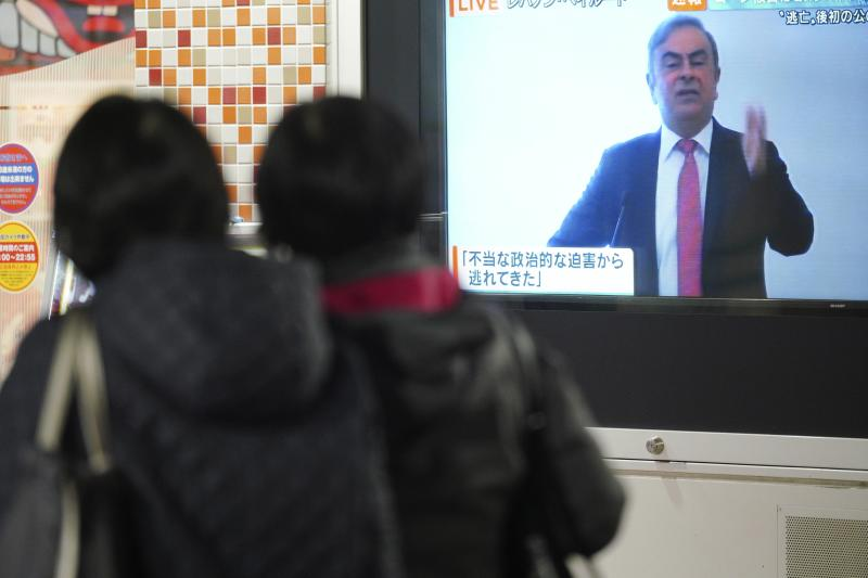 People in Tokyo watch a public TV showing a live broadcast of former Nissan chairman Carlos Ghosn speaking from Lebanon at his press conference Wednesday, Jan. 8, 2020.  Ghosn fled to Lebanon from Japan where he is facing charges of financial misconduct, managing to skip bail and leave Japan despite heavy surveillance in Tokyo. (AP Photo/Eugene Hoshiko)