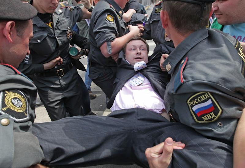 Russian police officers detain gay rights activist Nikolai Alexeyev during an attempt to hold a gay pride parade in Moscow, Russia, Sunday, May 27, 2012. Russian police have detained around a dozen protesters demanding the right to hold a gay pride parade in Moscow. Activists have long petitioned the Moscow government for permission to stage such a parade, but have always been denied. (AP Photo/Mikhail Metzel)