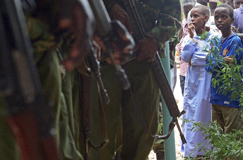 People look at Kenyan Defence Force officers, as they gather to view the bodies of the suspected attackers on a university in the northeastern town of Garissa, April 4, 2015 (AFP Photo/Carl De Souza)