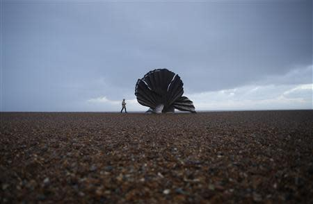 A woman looks at Scallop (2003) by sculptor Maggi Hambling, a tribute to composer Benjamin Britten, on Aldeburgh beach, eastern England November 21, 2013. REUTERS/Olivia Harris