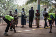 Electoral workers lay down tape as voters start to queue for presidential and legislative elections, at the Lycée Boganda polling station in the capital Bangui, Central African Republic Sunday, Dec. 27, 2020. President Faustin Archange Touadera and his party said the vote will go ahead after government forces clashed with rebels in recent days and some opposition candidates pulled out of the race amid growing insecurity. (AP Photo)