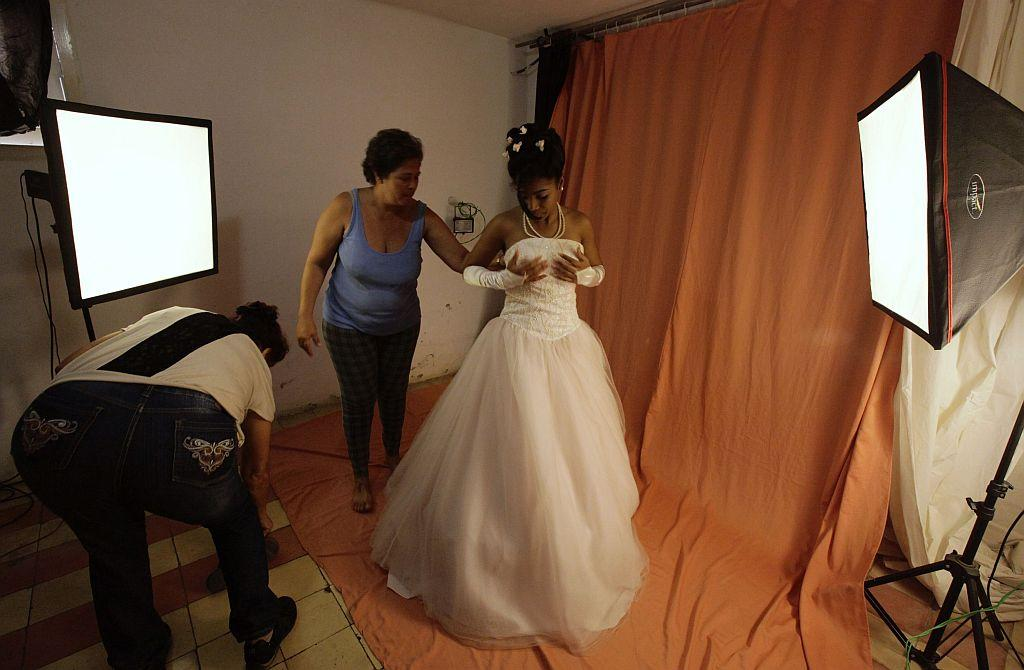 <p>Carmen Gonzalez (R) adjusts her dress during a photo session for her quinceanera.</p>