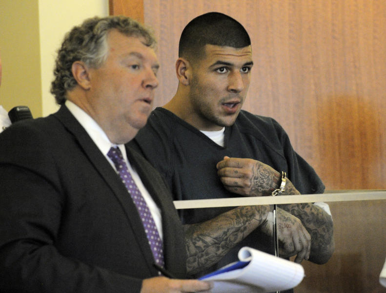 Former New England Patriots football player Aaron Hernandez, right, stands with his attorney Michael Fee, during a bail hearing in Fall River Superior Court Thursday, June 27, 2013, in Fall River, Mass. Hernandez, charged with murdering Odin Lloyd, a 27-year-old semi-pro football player, was denied bail. (AP Photo/Boston Herald, Ted Fitzgerald, Pool)
