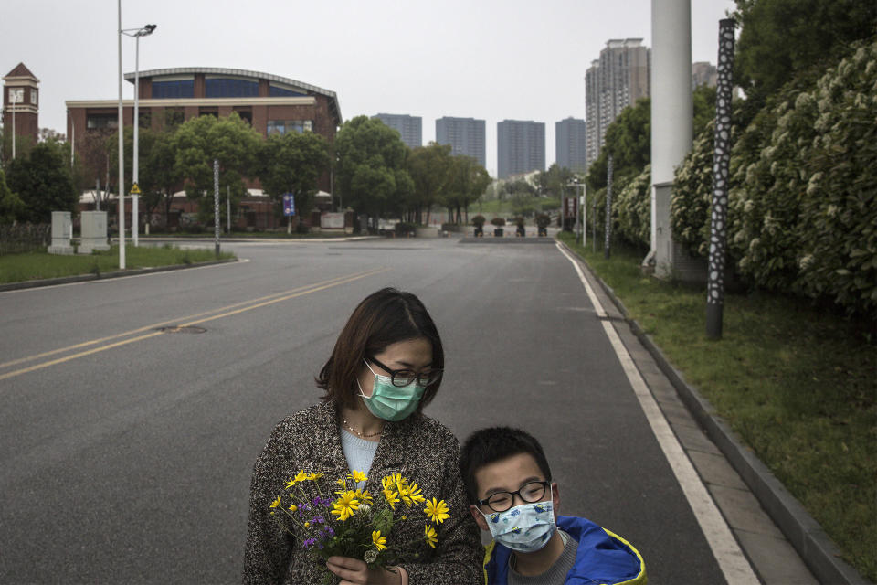 Image: A mother holds flowers while out on a walk with her son on March 31, 2020 in Hubei Province, China. Wuhan, (Getty Images file)