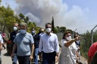 Greece's Prime Minister Kyriakos Mitsotakis, center, accompanied by Culture Minister Lina Mendoni, right, and Minister for Citizen Protection Michalis Chrisochoidis, left, visit the ancient Olympia during a wildfire in western Greece, Thursday, Aug. 5, 2021. Wildfires rekindled outside Athens and forced more evacuations around southern Greece Thursday as weather conditions worsened and firefighters in a round-the-clock battle stopped the flames just outside the birthplace of the ancient Olympics. (Giannis Spyrounis/ilialive.gr via AP)