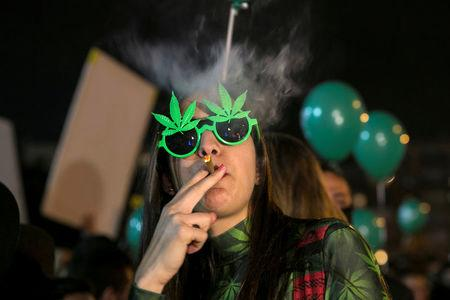 FILE PHOTO: A woman smokes during an event marking Israel's government's approval of a new policy to decriminalize personal marijuana use in Tel Aviv, Israel, February 4, 2017. REUTERS/Baz Ratner/File Photo