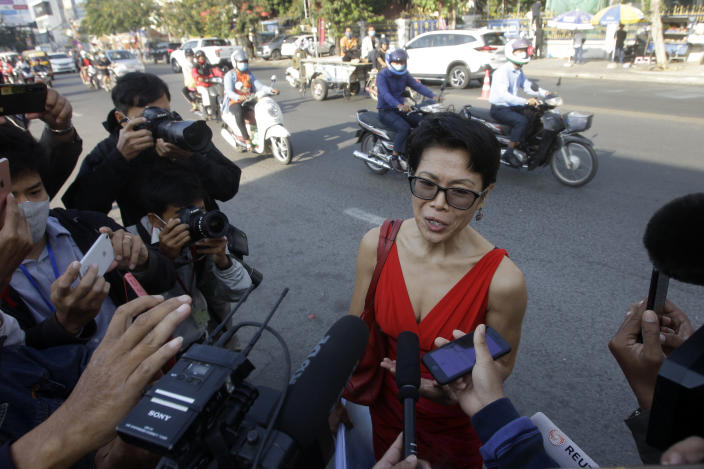 Theary Seng, center, a Cambodian-American lawyer, talks with journalists as she arrives in front of Phnom Penh Municipal Court in Phnom Penh, Cambodia, Thursday, Jan. 14, 2021. Theary Seng said Thursday she was being persecuted for her political opinion as she and dozens of other government critics charged with treason and other offenses returned to court in a trial criticized by rights advocates. (AP Photo/Heng Sinith)