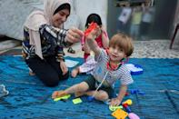 Maysa Abu al-Awf (L) plays with her two-year-old brother Ahmad and seven-year-old sister Maram at their grandfather's home in Gaza City, after their own home was demolished in an Israeli air strike that killed two of their sisters
