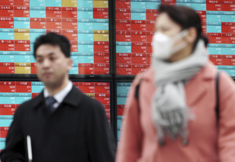 A man and a woman walk past an electronic stock board showing Japan's Nikkei 225 index at a securities firm in Tokyo Tuesday Feb. 26 2019. Most Asian share benchmarks are lower as a rally spurred by the Trump administration's decision to hold