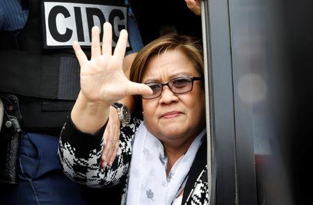 Philippine Senator Leila De Lima waves from a police van after appearing at a Muntinlupa court on drug charges in Muntinlupa, Metro Manila