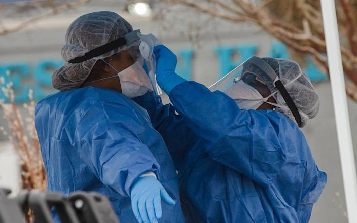 Healthcare workers from the Medical University of South Carolina clean each other's gear at a Covid-19 testing site - Bloomberg