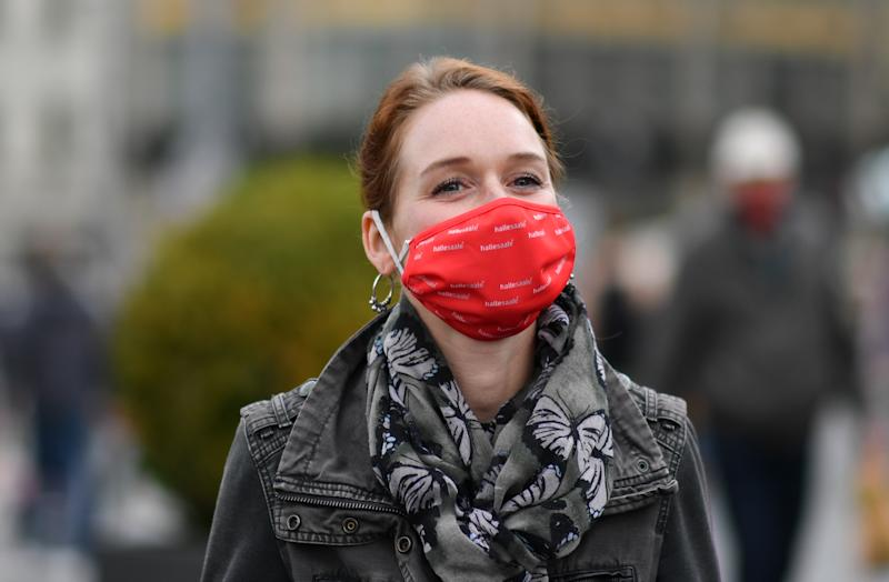 30 April 2020, Saxony-Anhalt, Halle (Saale): Carolin Loh from the Halle City Marketing Department wears a reusable temporary mouth and nose mask with the Halle/Saale city brand on the city's market square. The red masks are available at the tourist information office and are proving to be a real hit: in the city on the Saale, as in the whole country, masks are compulsory for public transport and in trade. Photo: Hendrik Schmidt/dpa-Zentralbild/dpa (Photo by Hendrik Schmidt/picture alliance via Getty Images)