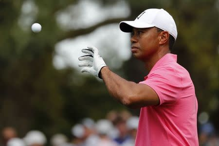 Tiger Woods of the U.S. catches a ball from his caddie on the first hole during practice for the 2018 Masters golf tournament at Augusta National Golf Club in Augusta, Georgia, U.S. April 2, 2018. REUTERS/Jonathan Ernst