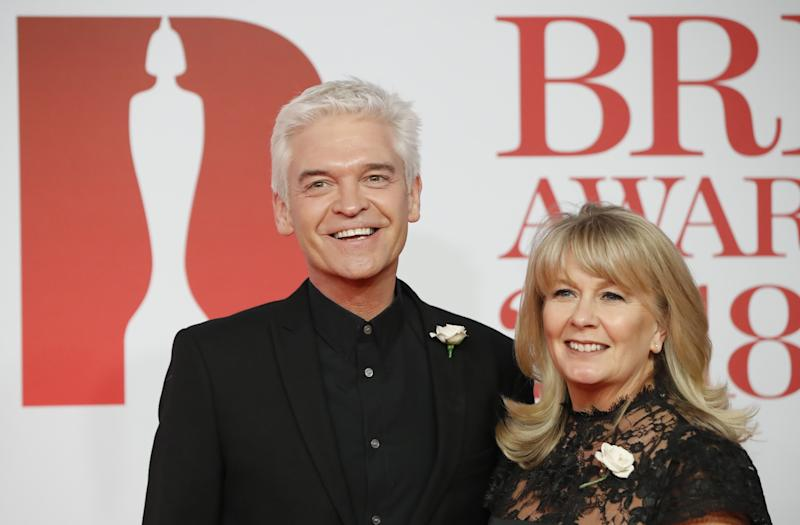 British television presenter Phillip Schofield and his wife Stefanie Lowe (R) pose on the red carpet on arrival for the BRIT Awards 2018 in London on February 21, 2018. / AFP PHOTO / Tolga AKMEN / RESTRICTED TO EDITORIAL USE NO POSTERS NO MERCHANDISE NO USE IN PUBLICATIONS DEVOTED TO ARTISTS (Photo credit should read TOLGA AKMEN/AFP via Getty Images)