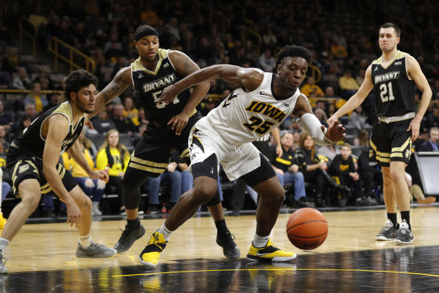 Iowa forward Tyler Cook (25) runs down a loose ball ahead of Bryant's Joe Kasperzyk, left, SaBastian Townes (54) and Tanner Johnson (21) during the second half of an NCAA college basketball game Saturday, Dec. 29, 2018, in Iowa City, Iowa. Iowa won 72-67. (AP Photo/Charlie Neibergall)