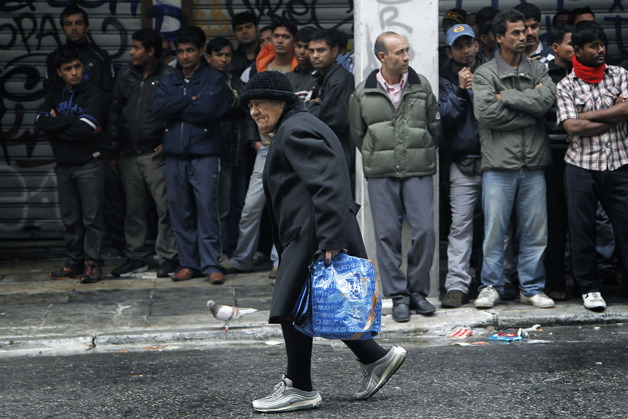 A woman walks past a group of suspected illegal immigrants detained during a police roundup in central Athens.