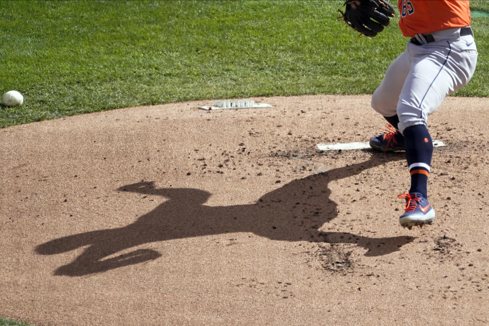 Houston Astros pitcher Jose Urquidy's shadow displays on the mound as he throws against the Minnesota Twins in the first inning of an American League wild-card series baseball game, Wednesday, Sept. 30, 2020, in Minneapolis. (AP Photo/Jim Mone)