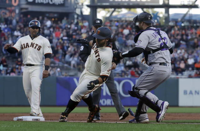 Colorado Rockies catcher Chris Iannetta, right, tags out San Francisco Giants' Brandon Crawford during a rundown in the third inning of a baseball game in San Francisco, Tuesday, June 25, 2019. (AP Photo/Jeff Chiu)