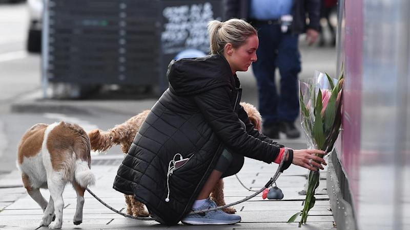 A woman places a floral tribute at the scene where a Dutch cyclist was killed in South Yarra