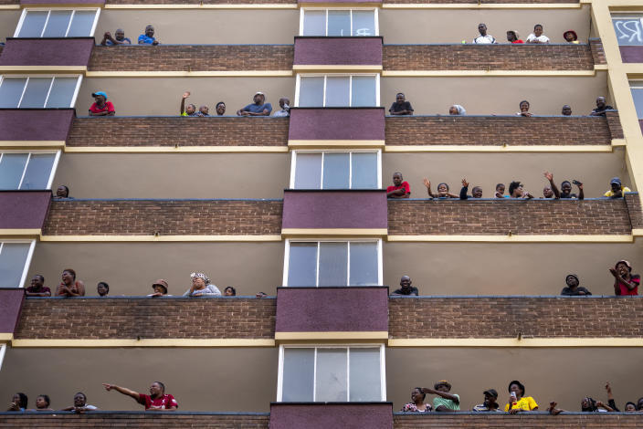 Residents of the densely populated Hillbrow neighborhood of downtown Johannesburg, confined in an attempt to prevent the spread coronavirus, stand and wave from their balconies, Friday, March 27, 2020. South Africa went into a nationwide lockdown for 21 days in an effort to mitigate the spread to the coronavirus. The new coronavirus causes mild or moderate symptoms for most people, but for some, especially older adults and people with existing health problems, it can cause more severe illness or death. (AP Photo/Jerome Delay)