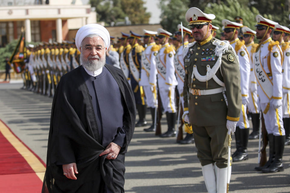 """In this photo released by the official website of the office of the Iranian Presidency, President Hassan Rouhani reviews an honor guard at the Mehrabad airport while leaving Tehran, Iran, for New York to attend United Nations General Assembly, Monday, Sept. 23, 2019. Rouhani, before traveling to attend the U.N. meetings, said Monday that Iran will invite """"all littoral states of the Persian Gulf"""" to join its coalition """"to guarantee the region's security."""" (Iranian Presidency Office via AP)"""