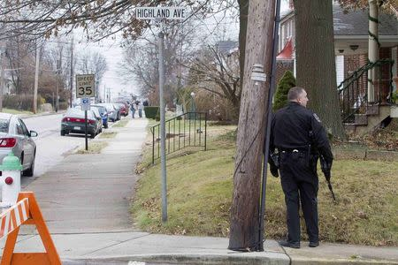 A police officer patrols near a home in a suburb of Philadelphia where a suspect in five killings was believed to be barricaded in Souderton, Pennsylvania, December 15, 2014. REUTERS/Brad Larrison