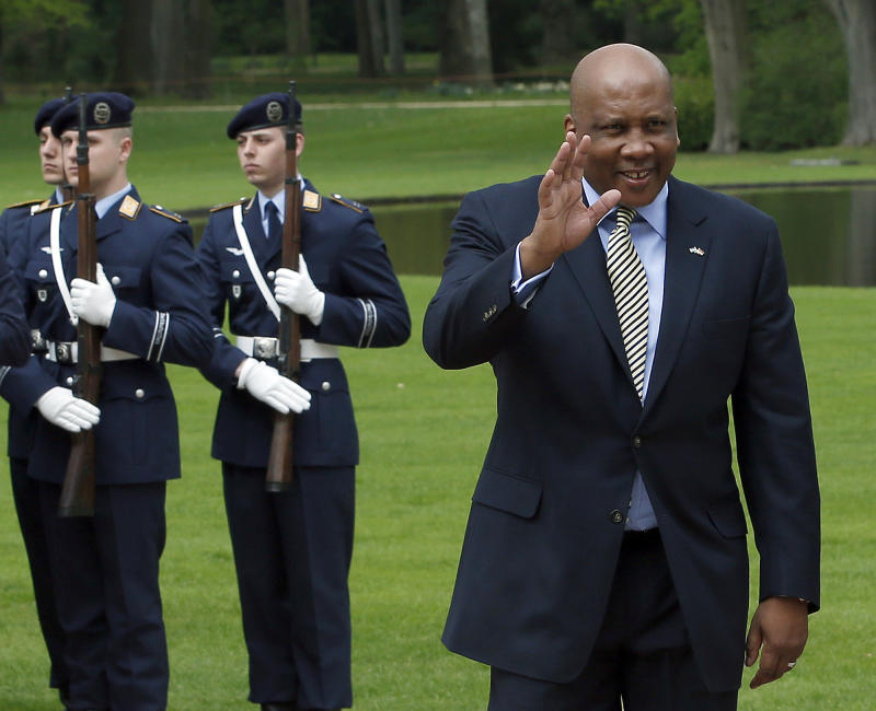 FILE - In this April 29, 2013, file photo, King Letsie III of Lesotho, right, waves in front of military honors at the Bellevue Palace in Berlin, Germany. The poor, mountainous kingdom encircled by South Africa has had a ceremonial, constitutional monarchy throughout decades of political instability since its independence from Britain in 1966. King Letsie III has openly criticized politicians for manipulating the military and shown interest in a more active political role. (AP Photo/Michael Sohn, File)