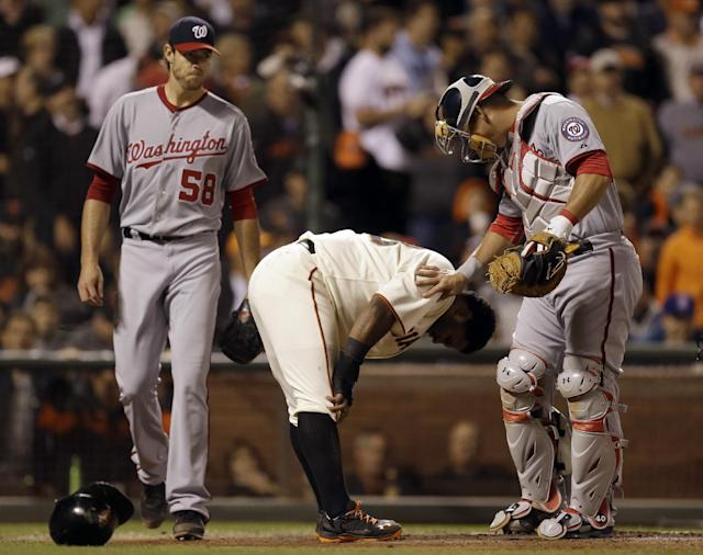 Washington Nationals catcher Wilson Ramos, right, tags checks on San Francisco Giants' Pablo Sandoval, center, whom Ramos tagged out at home plate in the sixth inning of a baseball game Tuesday, June 10, 2014, in San Francisco. Sandoval was attempting to score on a hit by Giants' Brandon Crawford. At left is Nationals pitcher Doug Fister. (AP Photo/Ben Margot)
