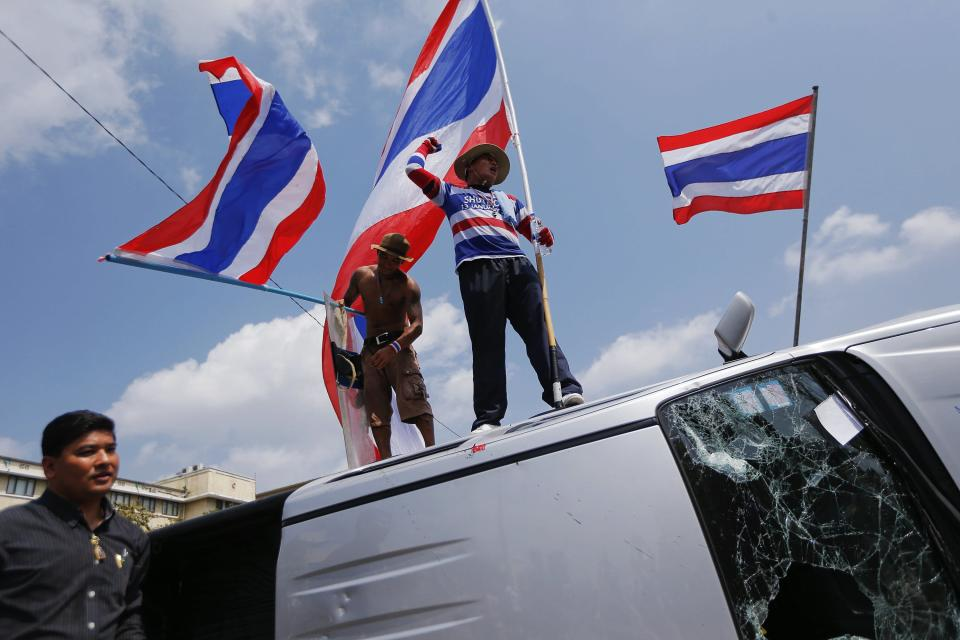 Anti-government protesters holding Thai flags celebrate atop an overturned police vehicle after clashes near the Government House in Bangkok February 18, 2014. A Thai police officer was killed and dozens of police and anti-government protesters were wounded in gun battles and clashes in Bangkok on Tuesday, officials and witnesses said. REUTERS/Damir Sagolj (THAILAND - Tags: POLITICS CIVIL UNREST)